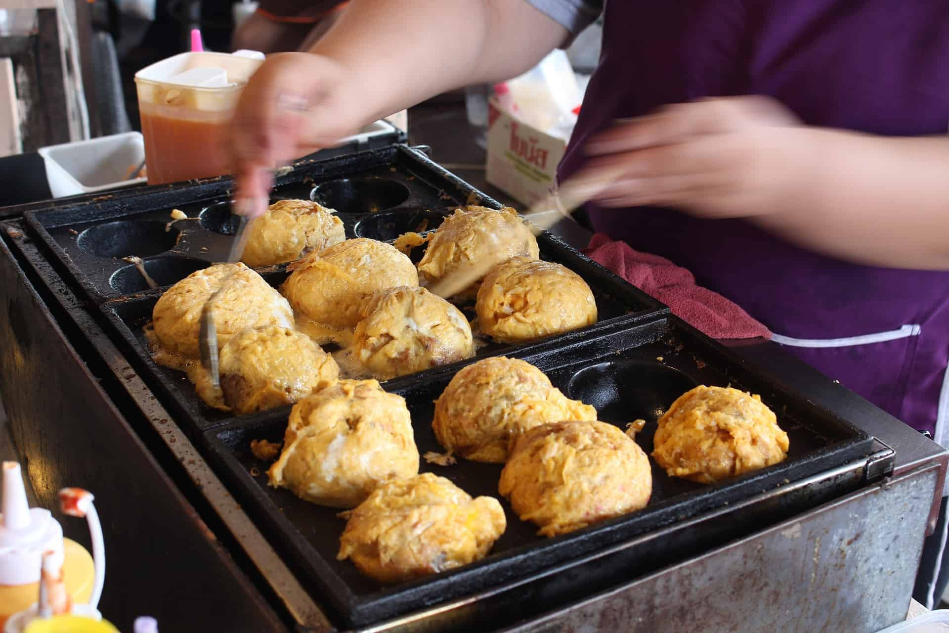 someone is making takoyaki with takoyaki pan