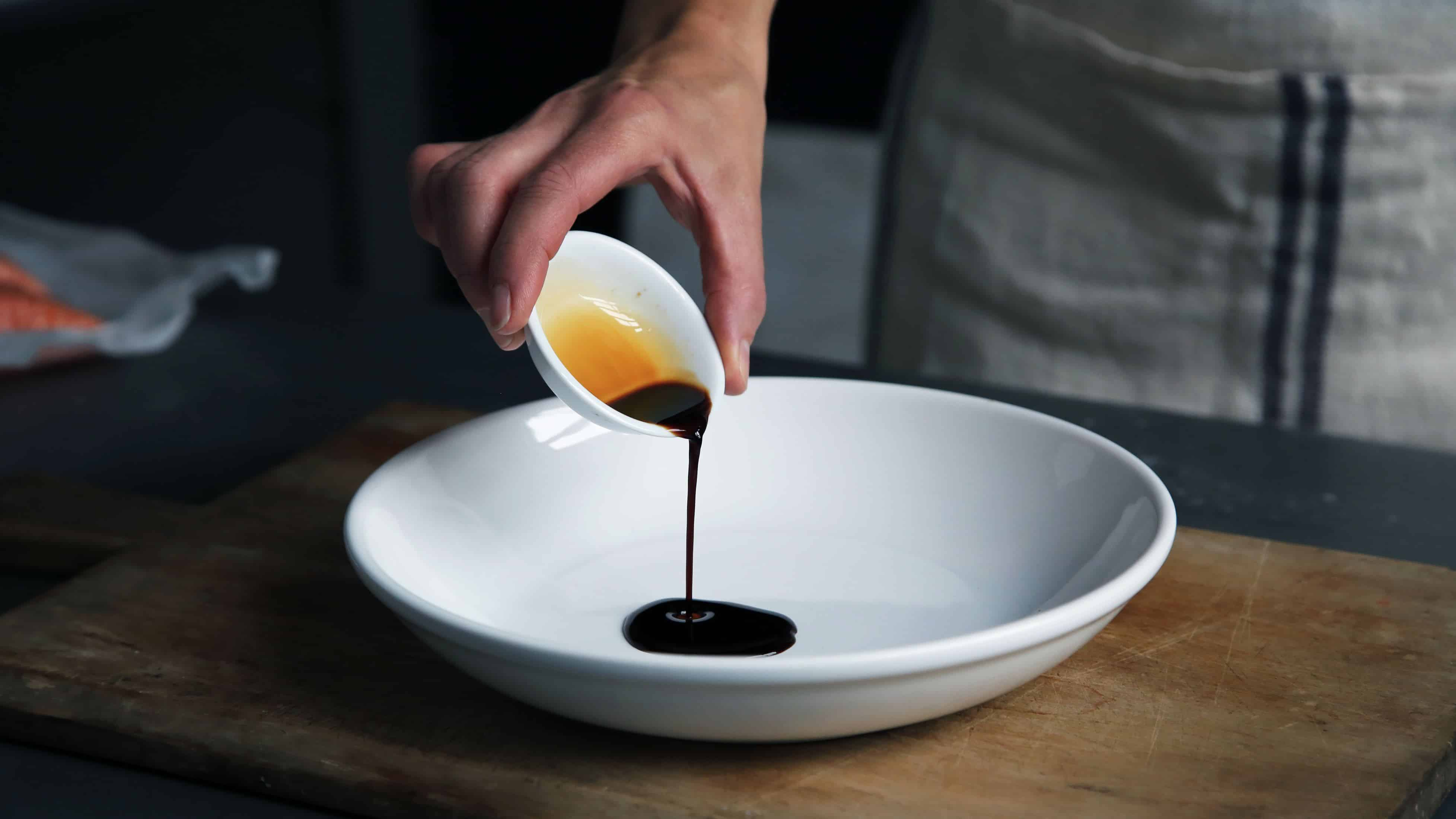 person dripping black liquid from small white ceramic bowl to big white ceramic bowl