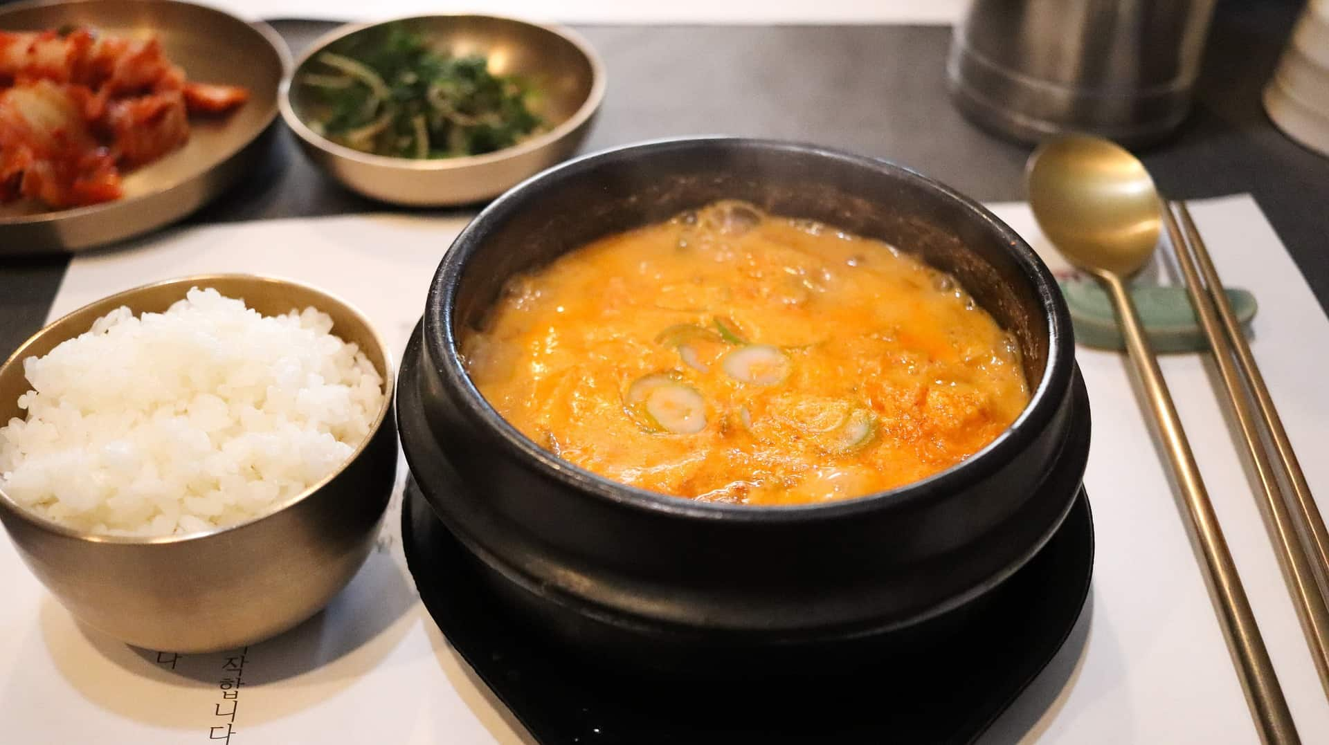 a dish in a traditional pot next to a small bowl of rice
