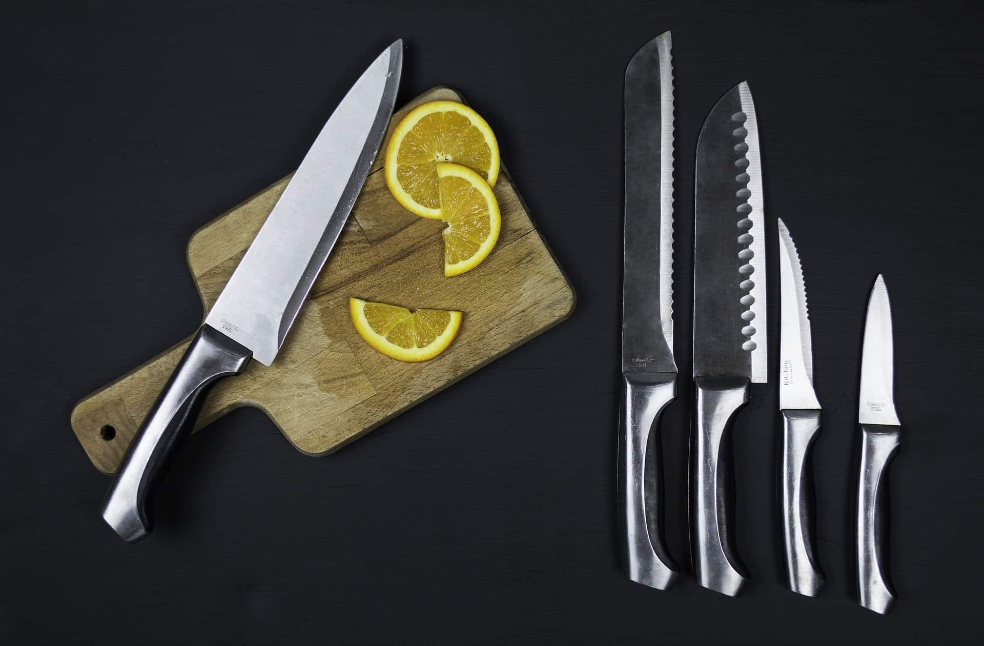 a cutting board with slice of lemons and knives set