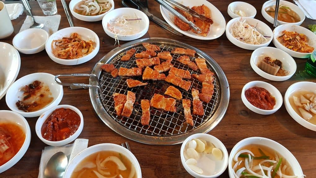 grilled meat in the middle surrounded by many korean dishes