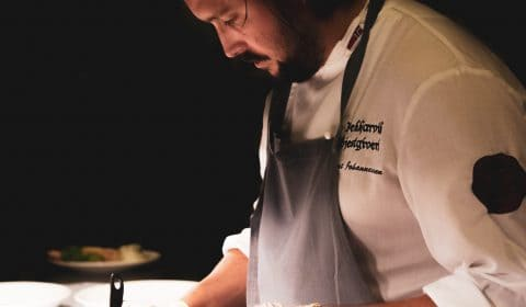 a chef is stirring something inside the pot