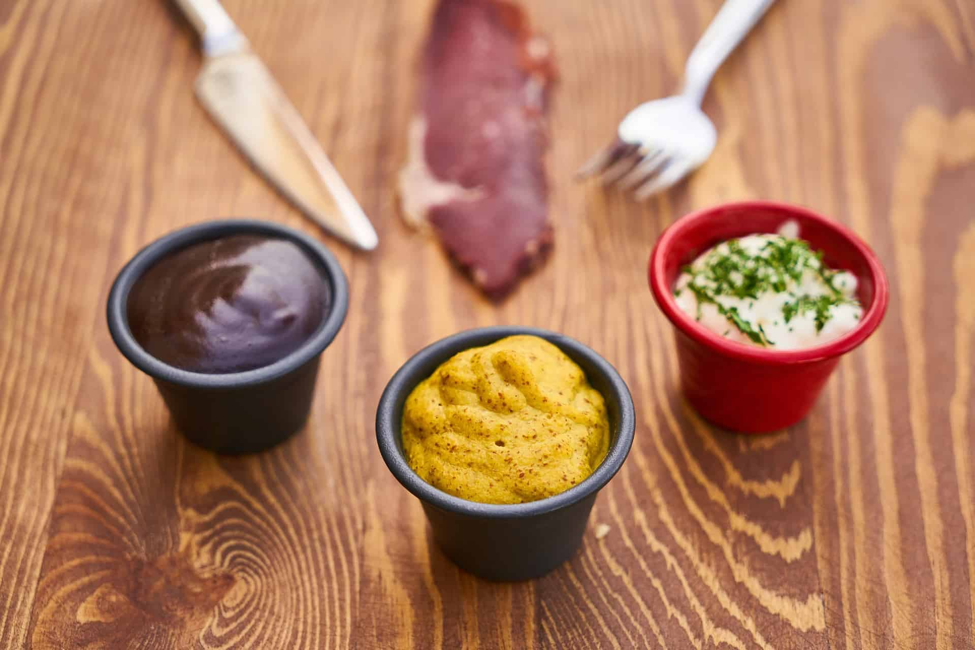 a mustard sauce along with other two sauces