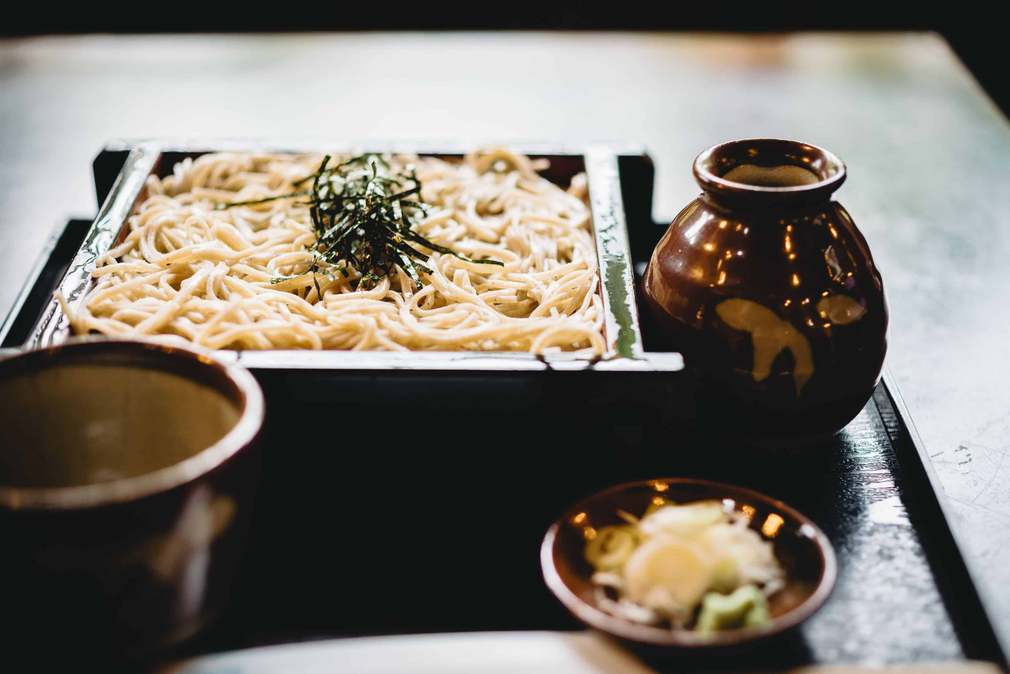 white pasta on black wooden plate with soba noodles