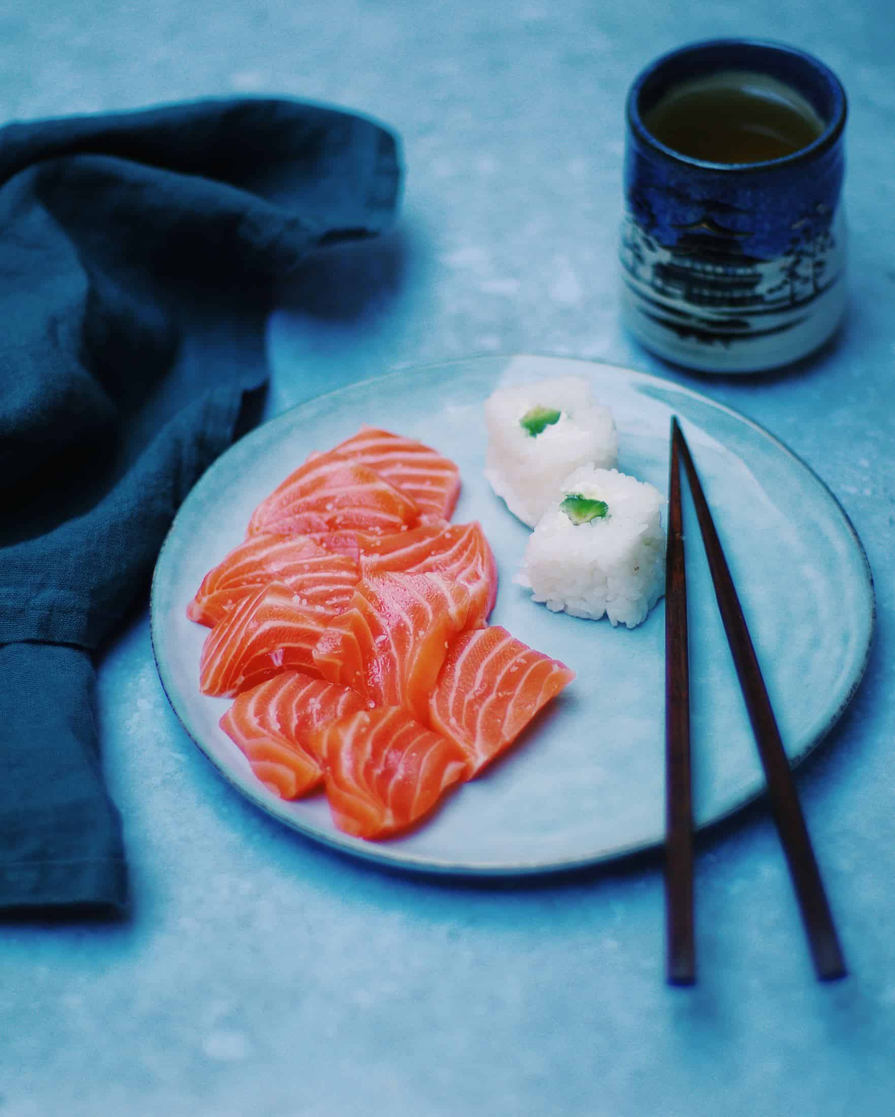 a plate of sashimi and sushi, and a glass of hot tea