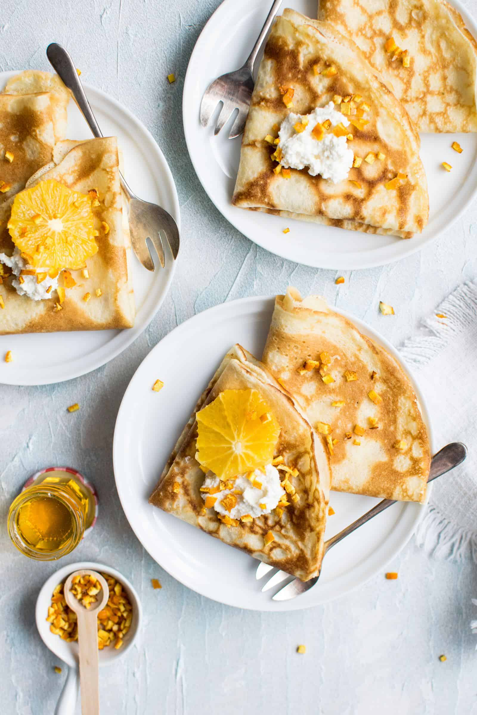 a few plates of crepes with oranges and honey as the toppings
