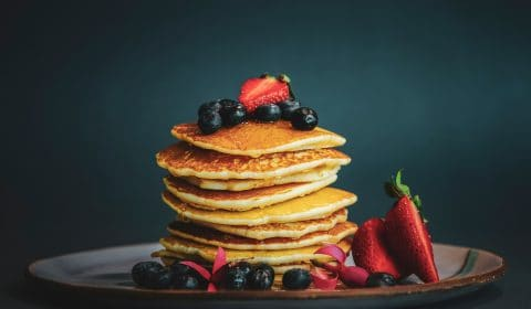 a plate of pancakes with blueberries and strawberries
