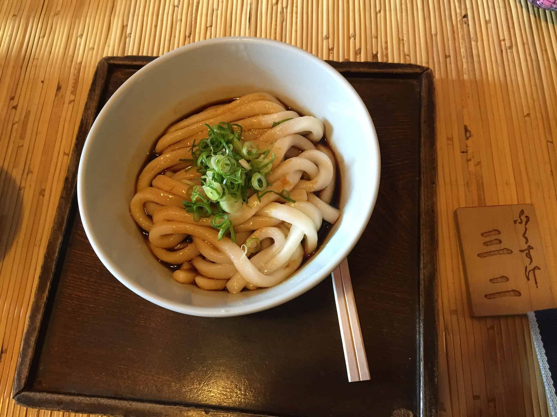 a bowl of udon on a black tray
