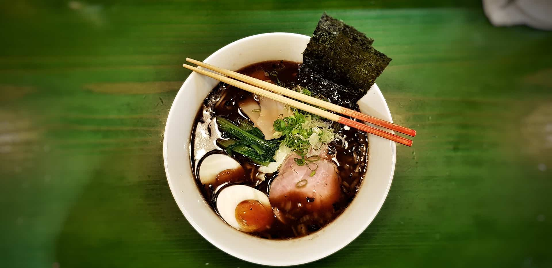 a bowl of ramen contained of eggs, meat, seaweed, with a black-color soup
