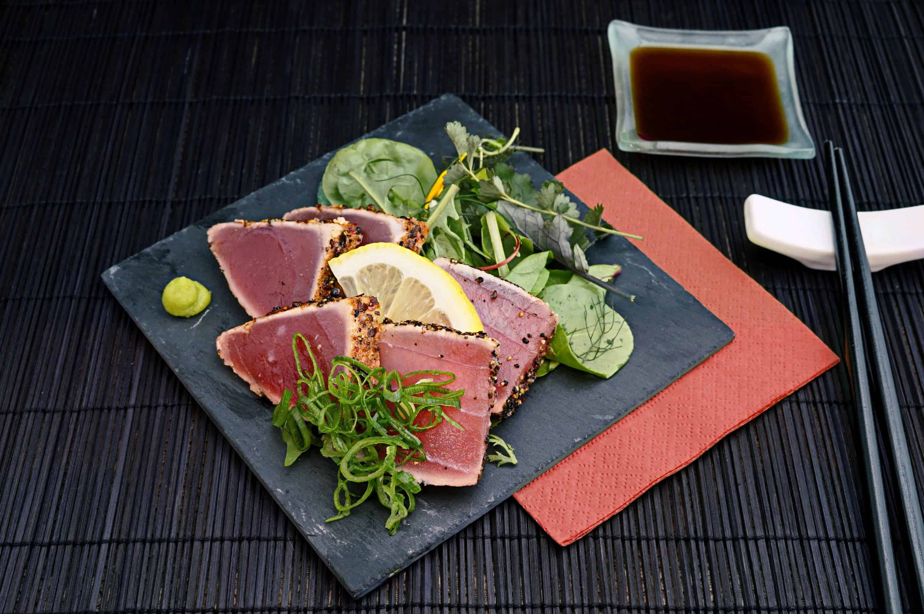 a plate of sashimi and vegetables with soy sauce and chopsticks next to it