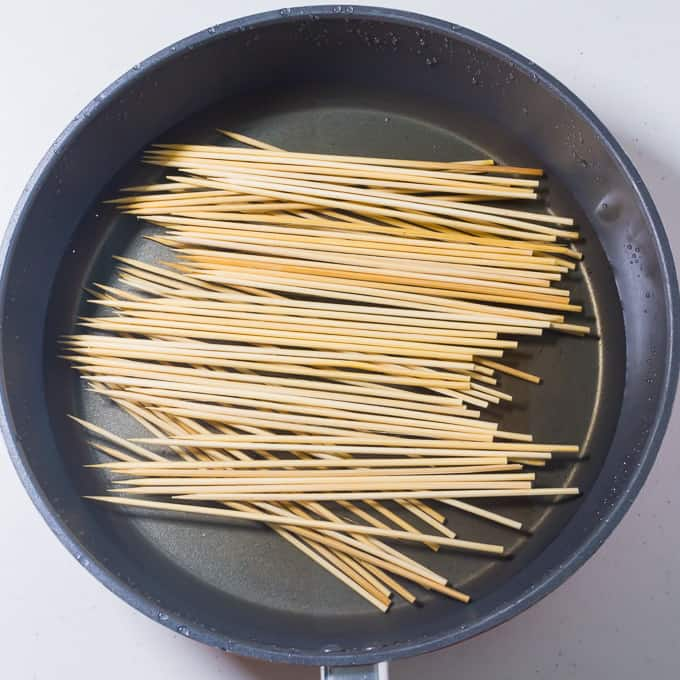 Soaking bamboo barbecue skewers in water
