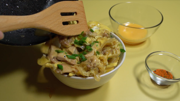 Serving the oyakodon in a bowl from the skillet
