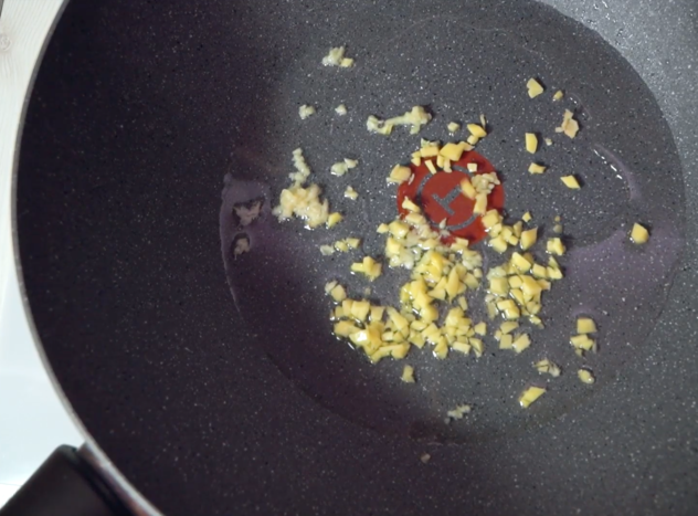 Heat the wok, add the oil and fry the minced garlic and ginger for approximately 30 seconds.